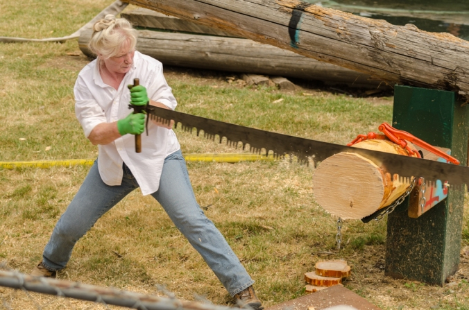 This woman was working very hard with her partner to saw through this log.