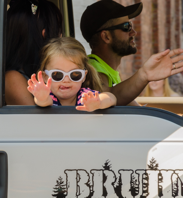 She is having a great time being in the parade and waving to everyone along the way.