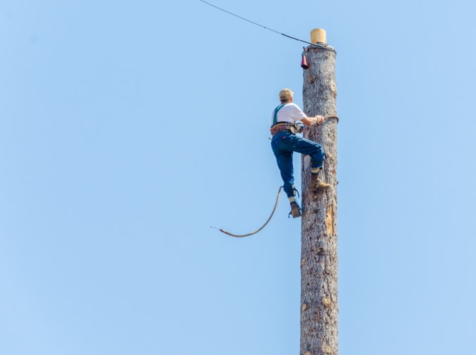 In this competition, people had to climb this large pole and then ring the bell at the top.