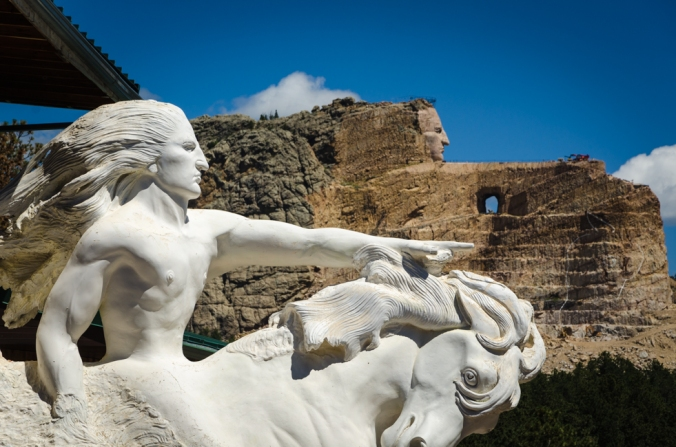 Crazy Horse. The white sculpture is the model and the background is where it is being carved from the mountain.